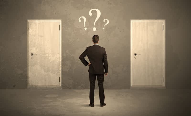 standing in front of two doors, unable to make the right decision concept with question marks above his head